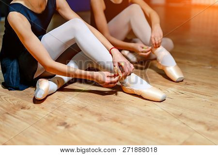 Young Ballet Dancers Tying Slippers Around Their Ankles On The Floor. Girls Sitting On The Floor And