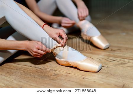 Two Ballet Girls Putting On Her Pointe Shoes Sitting On The Wooden Floor. Ballet Dancers Tying Balle