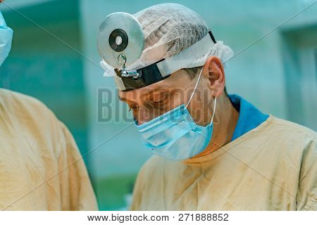Surgeon Man Dressed In Medical Clothes With Magnifying Glass On His Head In Operating Room. Surgeons