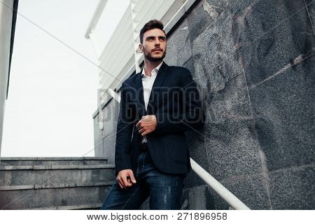 Young Stylish Businessman Man With A Beard In A Fashionable Suit And Jeans. Modern Image Of Business