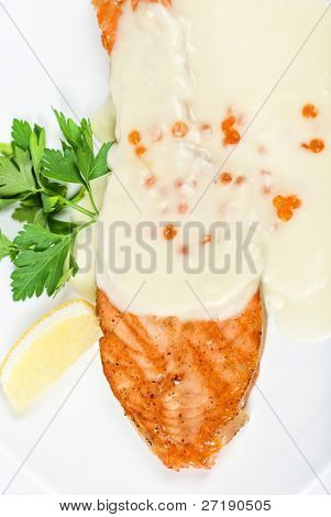 Grilled salmon steak with cheese sauce, greens, lemon and red caviar poster
