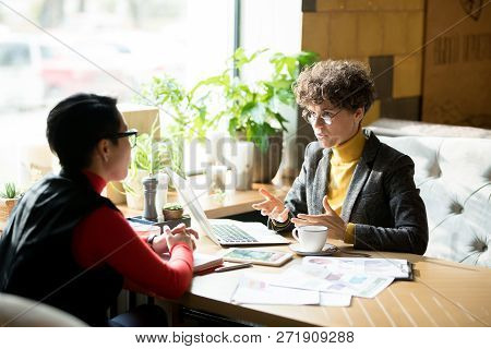 Serious Confident Female Business Analyst With Curly Hair Wearing Stylish Jacket Sitting At Table In