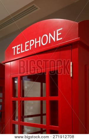 Traditional Red Telephone Booth Stands Indoors As A Symbol Of London And The Uk