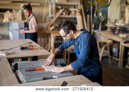 High angle portrait of mature carpenter working with wood in joinery workshop, copy space poster