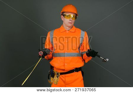 Guilty Builder Worker With A Meter And Hammer In Hands Justifies About Lateness Of Construction And