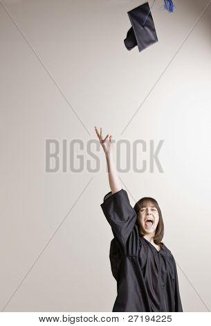 Female graduate throwing cap into the air