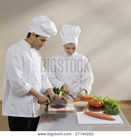 Male and female chef chopping vegetables