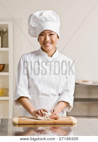 Chef en el toque y chef? s blancos amasar masa en cocinas
