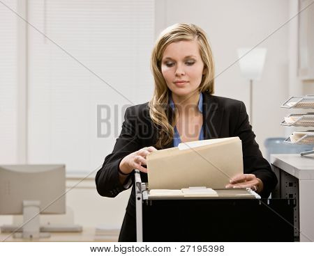 Serious businesswoman searches through file drawer for folder