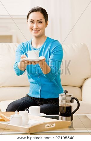 Hostess offering coffee to guest in livingroom