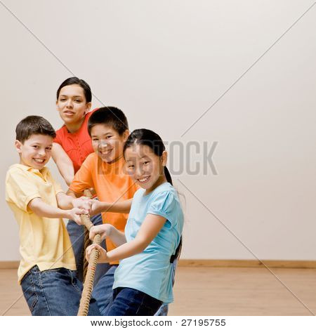 Determined children pulling on rope in tug-of-war