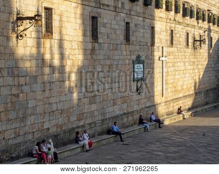 People Enjoy The Mild Autumn Weather On The Stone Bench Along The  Stark Wall Of The Convent Of San