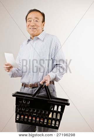 Confident man shopping for groceries with shopping list and holding basket