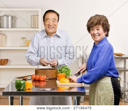 Helpful man preparing wholesome salad with wife in kitchen for dinner
