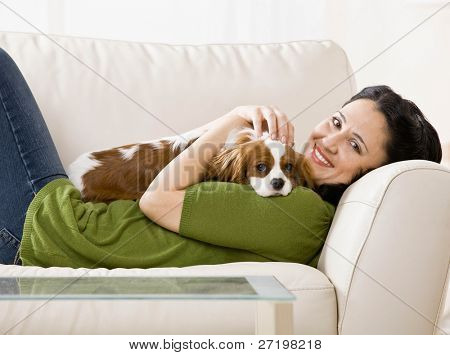 Relaxed woman laying on sofa holding and petting pet dog