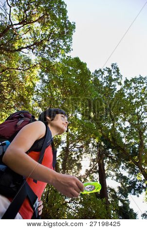 Woman with backpack using compass