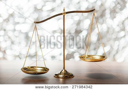 Gold brass balance scale,weight balance, imbalance scale on wooden desks with bokeh background. poster