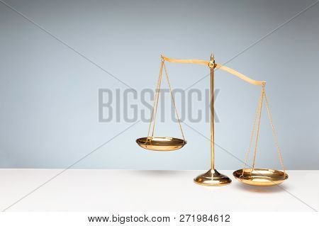 Gold brass balance scale, weight balance, imbalance scale and oval shadow on white desktop with gray background. poster