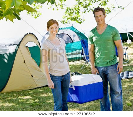 Couple carrying cooler at campsite