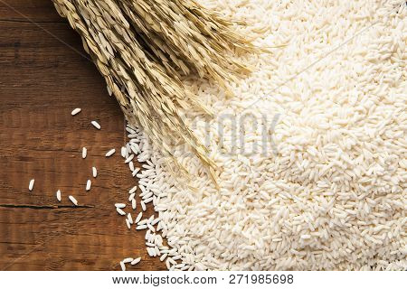 Close Up Of Jasmine Rice On Dark Wooden Table With Rice Plants, Ear Of Rice On White Jasmine Rice. T