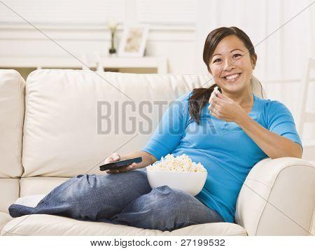 美しいアジアの女性は彼女の手で、リモートでポップコーンを食べて、ソファの上に座って。水平方向に