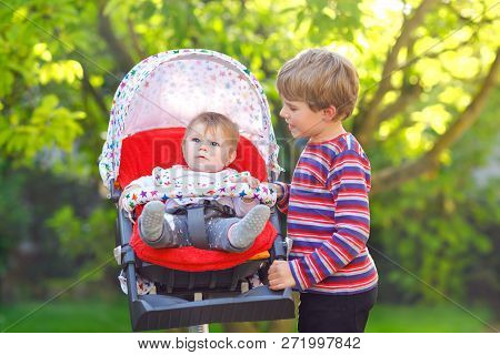 Little Blond Kid Boy Playing With Baby Sister. Happy Siblings In Garden. Baby Girl Sitting In Pram O