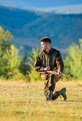 Hunter khaki clothes ready to hunt hold gun mountains background. Hunting shooting trophy. Hunter with rifle looking for animal. Man charging hunting rifle. Hunting as male hobby and leisure poster