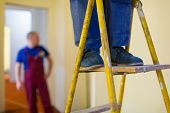 Legs of worker with blue workwear and black shoes on the wooden stepladder. Worker makes plasterboard or drywall for gypsum walls in apartment is under construction, remodeling, renovation, overhaul, extension, restoration and reconstruction. poster