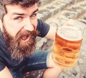 Guy raising up glass with draught beer. Hipster on cheerful face drinks beer outdoor. Celebration concept. Man with beard and mustache holds glass with beer while sits on stone stairs, defocused poster