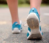 Close up motion shot of person walking away in running shoes poster