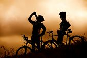 Attractive, healthy couple drink from their water bottles on mountain bikes, silhouette at sunset. active outdoor lifestyle concept poster