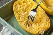 Scraping flesh of cooked spaghetti squash with fork on table poster