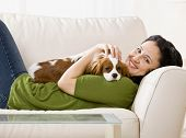 Relaxed woman laying on sofa holding and petting pet dog poster