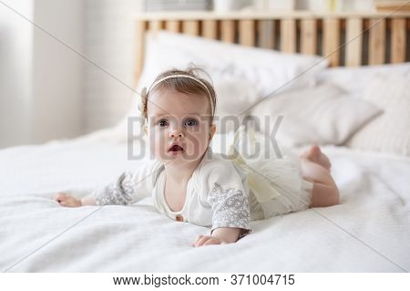 Adorable Baby Girl In White Sunny Bedroom Plays Alone Lying  On The Bed.charming Beautiful Lovely Sm