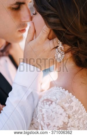 Close-up, The Wedding Couple Is Almost Kissing. The Groom Strokes The Brides Hand On The Cheek. Fine