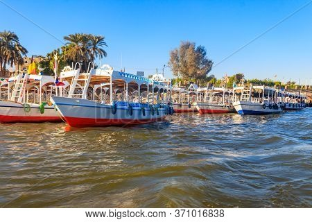 Tourist Boats Moored Near The Shore Of Nile River In Luxor, Egypt