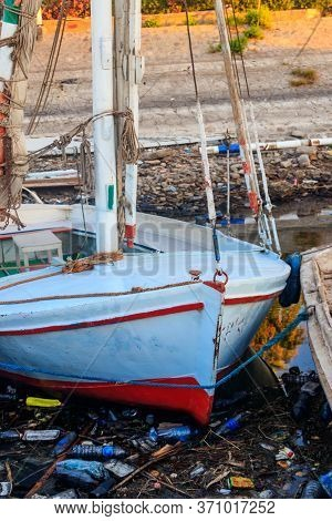Old Boats Moored In Dirty Harbour. Pollution Of River, Sea, Ocean Water With Waste, Plastics Garbage
