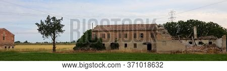 Ruins Of An Abandoned And Destroyed Farm In The Plain After The Industrialization Of Agriculture