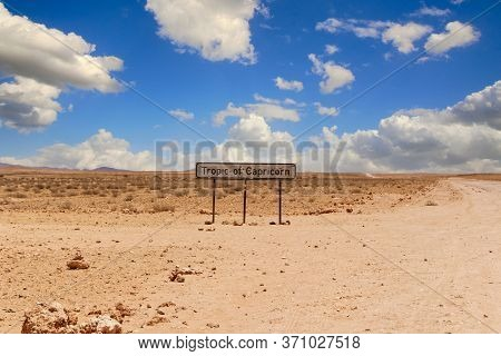 Tropic Of Capricorn Sign At A Desert Dirt Road In Namibia Under A Blue Sky Over The Sand On A Hot Da