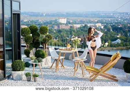 Attractive Woman In Black Bathing Suit And White Shirt Is Drinking Coffee Near Table With Breakfast