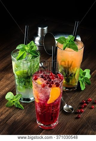 Three Alcoholic Cocktails Mojito And Cranberry Or Lingonberry Cocktail On A Wooden Background, Refre