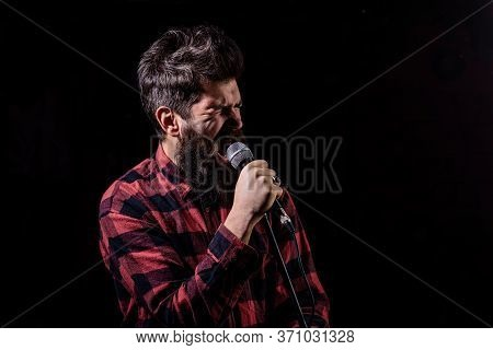Man With Tense Face Holds Microphone, Singing Song, Black Background.