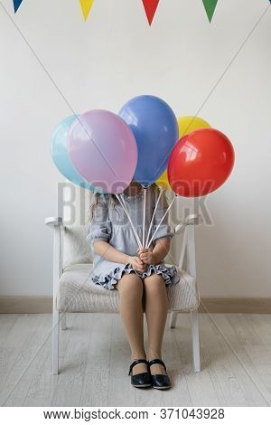Cute Little Girl On A Birthday Sitting On A White Armchair In A Room With An Armful Of Multi-colored