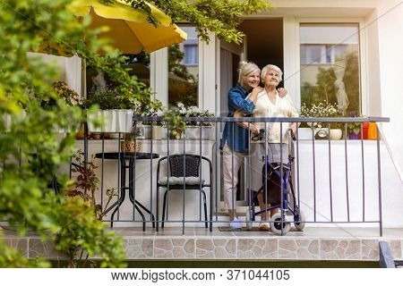 Senior woman and her adult daughter standing on balcony