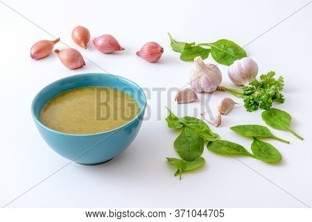 Turquoise Bowl With Spinach Soup And Raw Ingredients, Spice And Herbs. The Spinach Leafs, Onion Shal