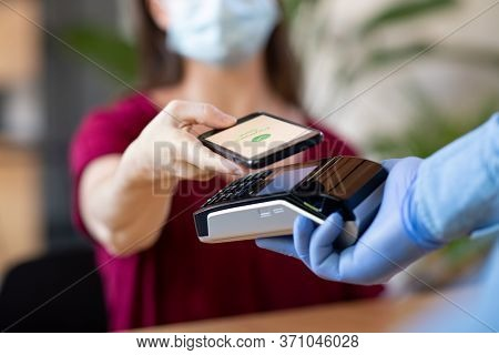 Cashier hand holding credit card reader machine and wearing disposable gloves while client holding phone for NFC payment. Woman wearing face mask while paying with smartphone during Covid-19 pandemic.