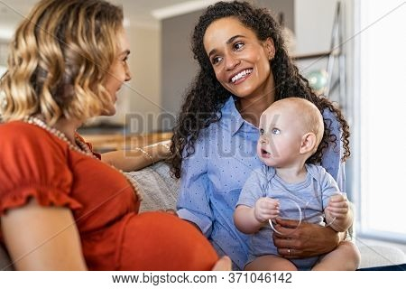 Happy multiethnic friends with child relaxing at home. Mixed race woman with expecting mother talking and playing with baby. Pregnant lesbian mothers smiling, assisted fertilization and reproduction.