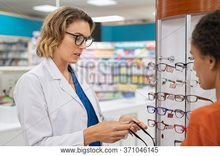 Young ophthalmologist helping woman to choose the most appropriate eyeglasses. African young woman buying new spectacles with help of optician in pharmacy store. Eyesight and vision eye care concept.
