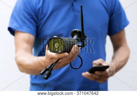 Security Cameras And Cctv Services - Technician With Ip Camera In Hand