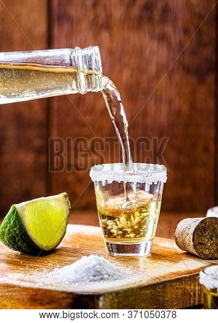 Tequila Bottle Filling Glass Of Drink. Typical Mexican Drink Being Served.